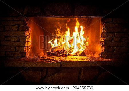 Yellow bright flames in the stone fireplace