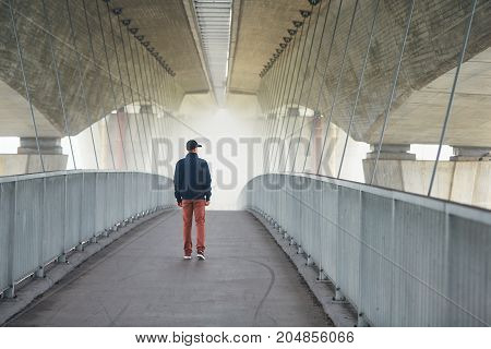 Man on the footbridge under highway bridge in mysterious morning fog. Prague Czech Republic