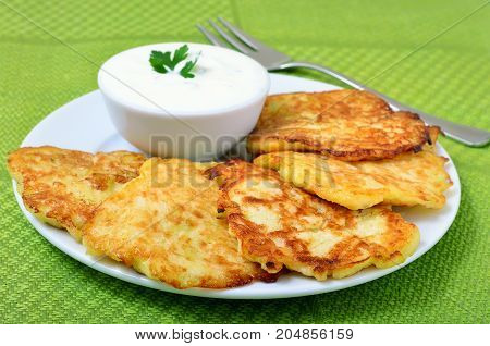 Fried zucchini pancakes and sauce on white plate