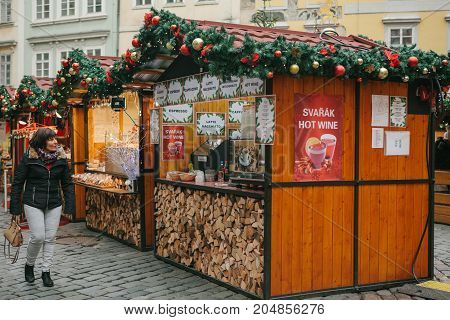 Prague, December 13, 2016: Old Town Square in Prague on Christmas Day. Christmas market in the main square of the city. The woman looks with amazement and joy at the decorated shopping tent with a huge selection of hot mulled wine and coffee drinks.