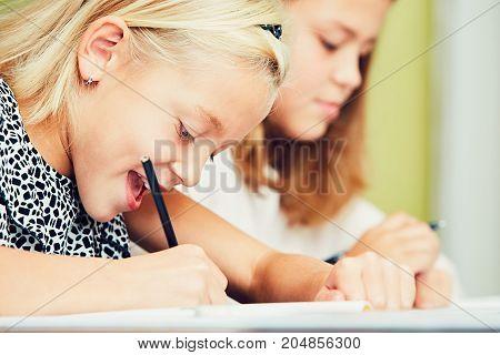 Little girls writing their homework for elementary school.
