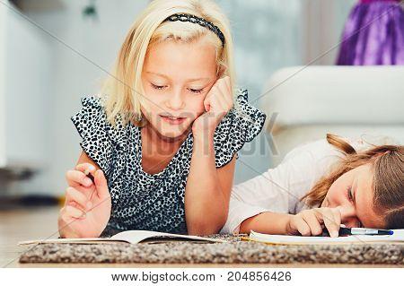 Girls lying on the carpet making their homework in elementary school.