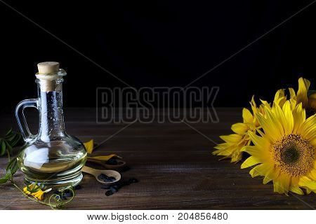 Sunflower oil in bottle glass with seed and flowers