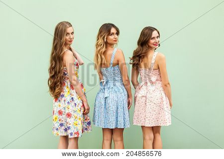 Three Young Female Friends In Cute Dresses Turned Over The Shoulder