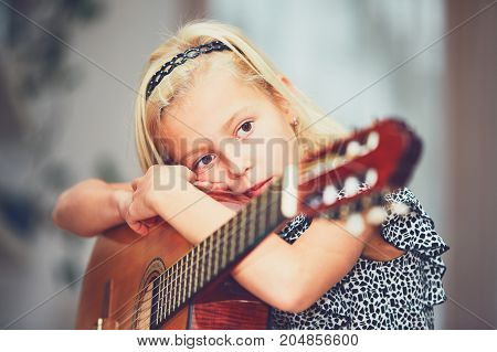 Tired little girl learning to play to the guitar at the home.