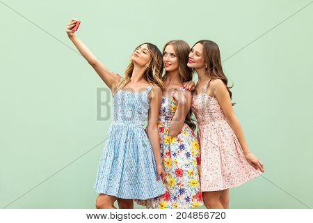 Hipsters Three Friends In Casual Dress, Macking Selfie On Green Background And Have Fun
