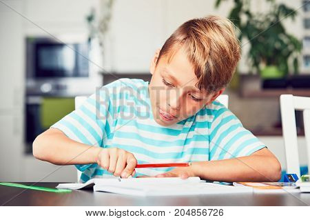 Little boy writing his homework for elementary school.