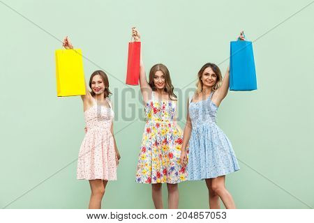 Young Adult Girl In Dress, Showing Her Bags After Shopping. Hands Up And Holding Her Colorful Bags.