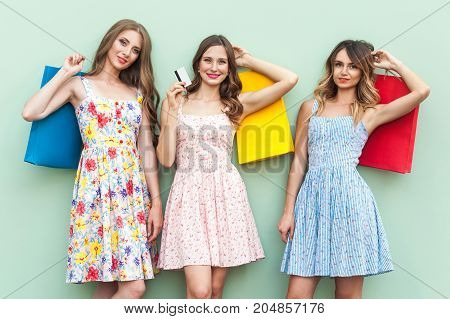 Showing Credit Cards. Sexy Girls In Dress, Standing In Front Of Green Background