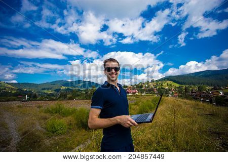 A young man working on a laptop outdoors high in the mountains with a beautiful sky in the background