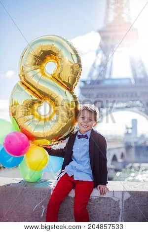 Happy boy with bunch of colorful balloons in Paris near the Eiffel tower.
