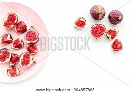 Fresh blue figs slices on plate on white background top view.