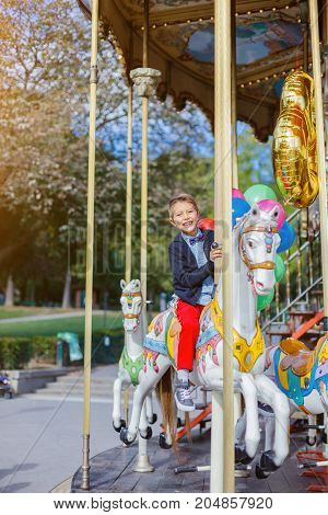 Happy boy with bunch of colorful balloons having fun on the carousel in Paris.