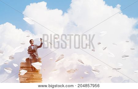 Funny man in red glasses and suit sitting on book and paper planes flying around