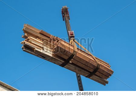 Crane Lifts Wooden Slats On The Roof, Blue Sky