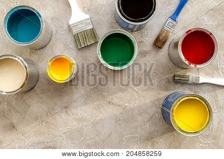 Paints in tin banks and brushes on grey stone background top view.