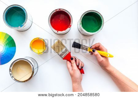 Choosing color for painting. Hands hold brush and paints on white background top view.
