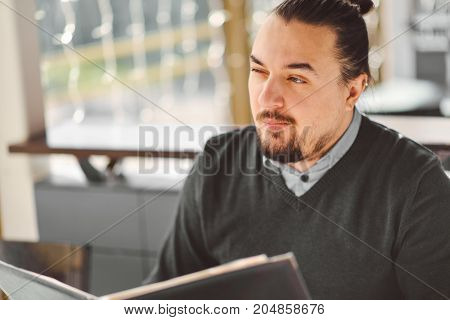 Young man looks at the menu in coffee shop