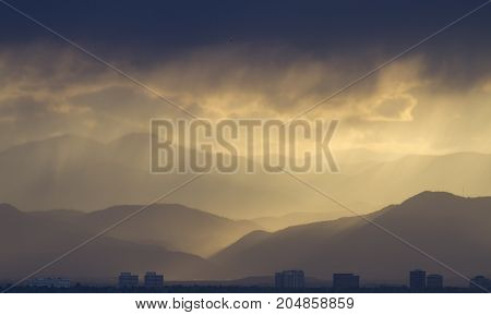 Storm Clouds over the Rocky Mountain with City Silhouette in Foreground