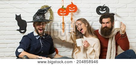 Halloween girl winking with long hair. Men serious and surprised sitting on floor. Friendship and people concept. Friends drinking tea and celebrating. Holiday traditional symbols on white brick wall.
