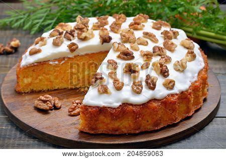 Homemade carrot cake with icing decorated walnut close up