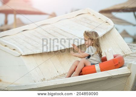 Happiness and expressive emotions. Childhood and baby care concept. Small kid sit on wooden boat at beach. Marine safety and transport. Boy little child sitting in life ring.