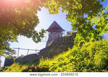 Landmark and travel destination. Castle tower and wall. Bastion on sunny summer day. Stone fortification on green hill on blue sky. Protection and defense concept.