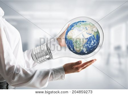 Cropped image of businessman in shirt holding lightbulb with Earth globe inside in hands with office view background. Elements of this image are furnished by NASA.