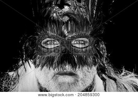 Male face with deep green eyes white beard and long hair in decorative masquerade vintage mask with brown and yellow feathers carnival on black background studio
