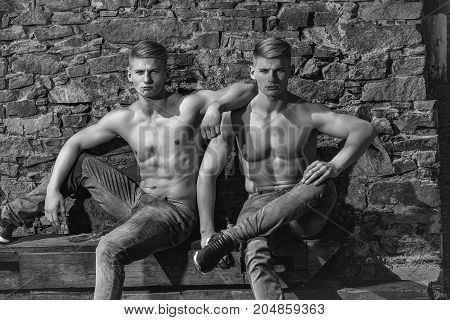 Sexy athletic young men serious twins brother posing in jeans without shirt on mural background