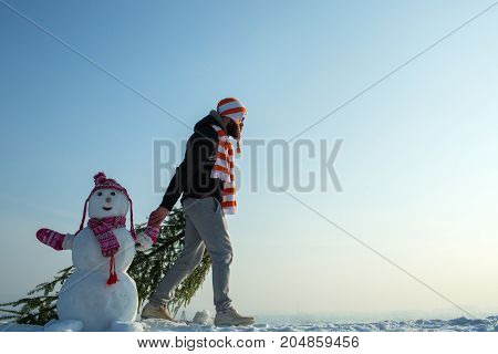 Man And Snowman Walking On Blue Sky
