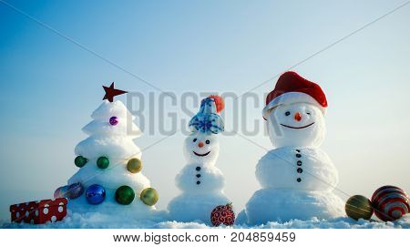 Snow sculptures with smiley faces in hats on winter day. Merry Christmas and happy new year. xmas tree decorated with star and balls. Holidays celebration concept. Snowmen on blue sky background.
