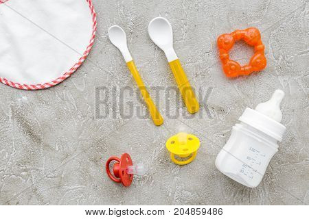 preparation of mixture baby feeding with infant formula powdered milk in bottle, spoon and toys on gray stone background top view