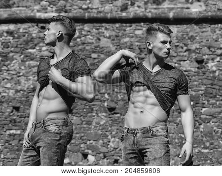 young twin brothers sexy models in jeans with bare torso and muscular body outdoor on mural background