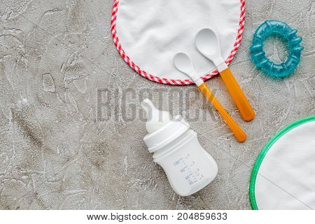 preparation of mixture baby feeding with infant formula powdered milk in bottle, spoon and toys on gray stone background top view mockup