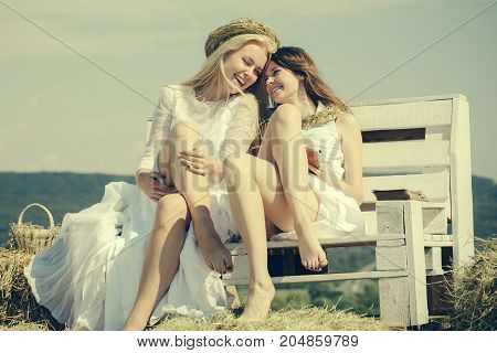 Women in white dresses on sunny day. Happy students on blue sky. Education and knowledge concept. Summer holidays and vacation. Two girls reading books on bench on hay.