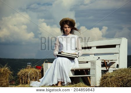 Woman typing on typewriter on cloudy sky. Girl in wreath and white dress on bench. Assistant or secretary working on nature on sunny day. Vintage equipment and archaism. Summer vacation concept.