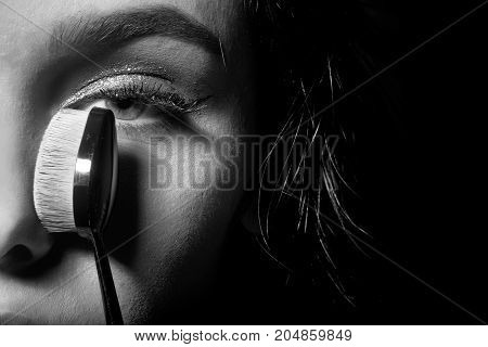 pretty woman or cute sexy girl with brunette hair has long eyelashes and fashionable eye makeup on adorable face holds foundation make up brush near face on black background. beauty and cosmetics