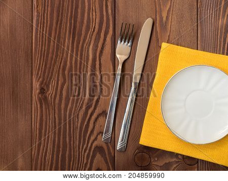 Empty plate on tablecloth on wooden table. View from above