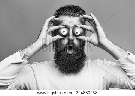 handsome bearded man with long lush beard and moustache on emotional face holding eggs as eyes in studio on grey background