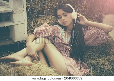 Lifestyle and technology. Girl listening music with closed eyes. Leisure and entertainment. Woman with headphones relaxing in hay. Summer vacation concept.