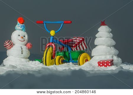 Snowman And Snow Xmas Tree On Grey Sky