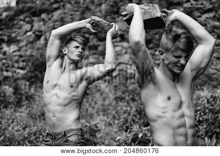 Muscular young twins with beautiful sexy body and bare torso standing outdoor holding stone in hand on green background