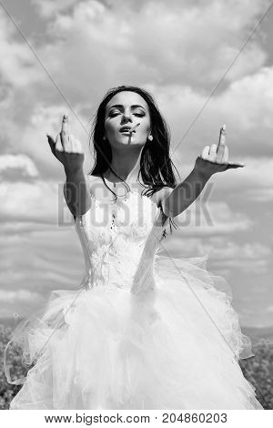 young wedding sexy girl woman with brunette hair and pretty face in white bride dress showing middle fingers smoking cigarette on cloudy blue sky natural background