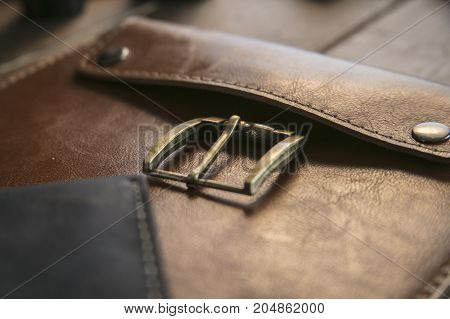 Perfection beauty. Close up of brown leather handmade handbag with bronze clasp on wooden table. Beautiful product of creative leather workshop
