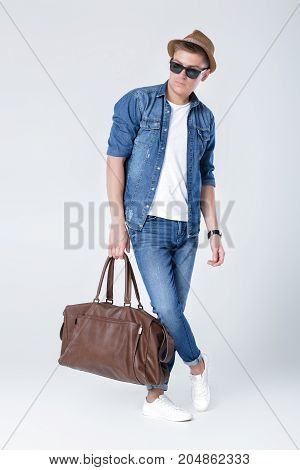Handsome young man in denim holding leather bag on grey background
