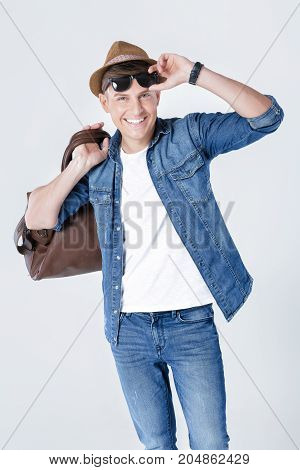 Handsome smiling man in hat and sunglasses carrying leather bag on shoulder on grey background