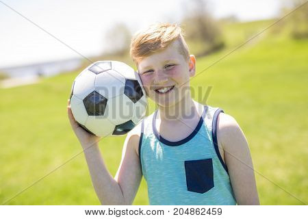 A boy holding foot ball in the park.