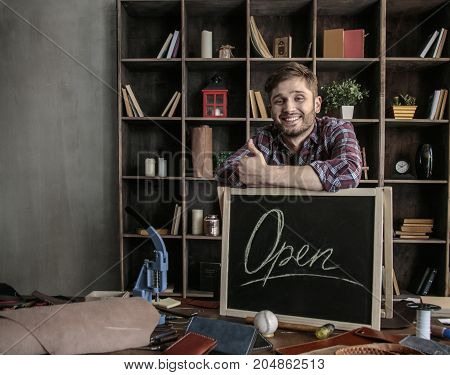 High spirits. Young joyful man leather worker standing near open sign at wooden table with leather tools in creative workshop and showing thumbs up. Creative workshop in office