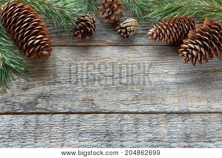 Pine cones and branches on wooden background Christmas background
